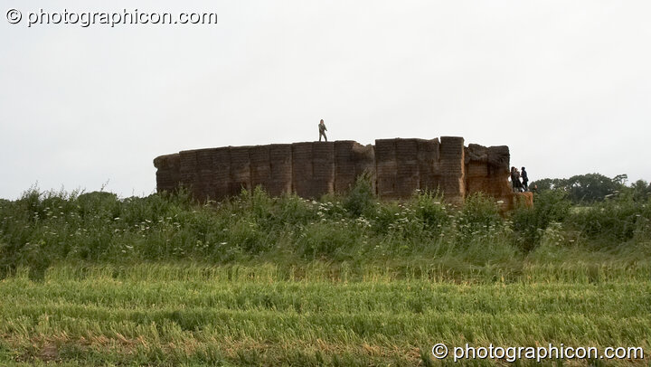 A person stands on top of a giant hay stack at the Echo Festival. Overton, Great Britain. © 2007 Photographicon