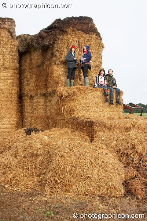 People enjoying the view from the side of a giant hay stack at the Echo Festival. Overton, Great Britain. © 2007 Photographicon