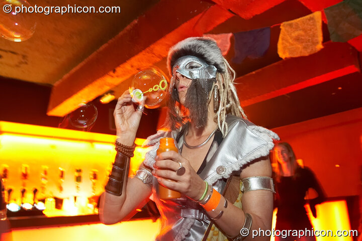 A woman playfully spins the bubbles she blows at the Pukka / Interpole / Mindscapes Halloween party. London, Great Britain. © 2007 Photographicon