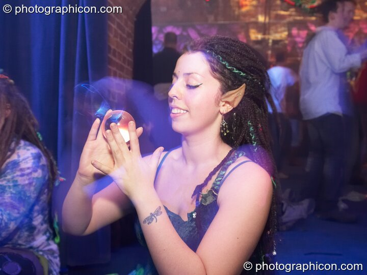 A woman with pixie ears plays with a clear contact ball in  Dakini Records & Gandalf's Garden Party room at Alpha Omega. London, Great Britain. © 2008 Photographicon