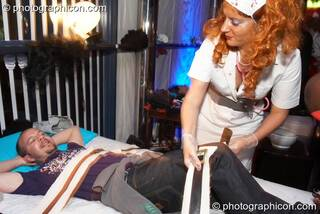 A man is strapped to a bed and given physco-theraputic beauty treatments by a wonky nurse in the Slumbarave Sanitarium at the Electric Circus. London, Great Britain. © 2010 Photographicon