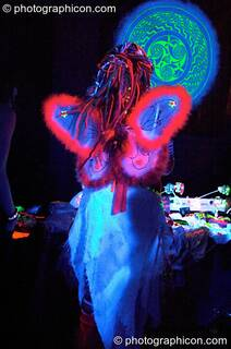 Girl dressed in winged angel outfit under UV light in the Liquid Connective space at the Synergy Project. London, Great Britain. © 2005 Photographicon