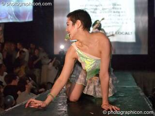 Woman kneels on the catwalk modelling for an ethical fashion show at The Synergy Project. London, Great Britain. © 2005 Photographicon
