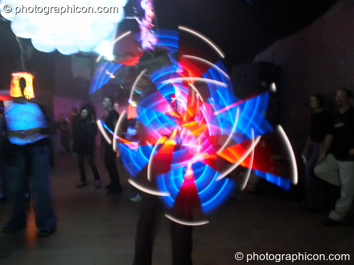 Jedi Juggler with illuminated flashing Glow Staffs, trail-blurred by slow shutter speed, at The Synergy Project. London, Great Britain. © 2006 Photographicon