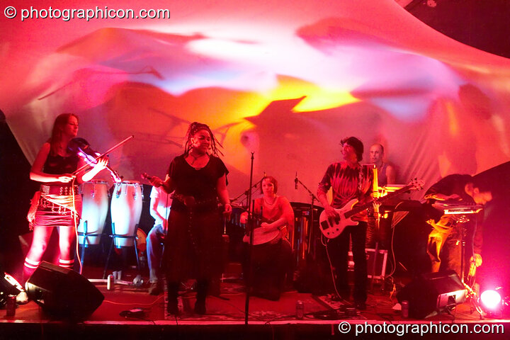 "Kate Farbon (violin), Jon ""Bongly"" Tubmen (percussion), Myo (vocals), Becky Dell (percussion), Pierre Luigi (bass), Pete Ardron (keyboards), and Bagz (electronic percussion) of Orchid Star on the Small World Stage at The Synergy Project. London, Great Britain. © 2006 Photographicon"