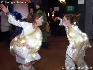 Two women wearing costumes covered in light bulbs dance at The Synergy Project. London, Great Britain. © 2007 Photographicon