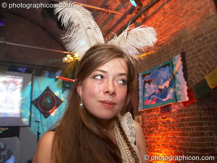 Woman with feathers in her hair takes a sideways glance at The Synergy Project. London, Great Britain. © 2007 Photographicon