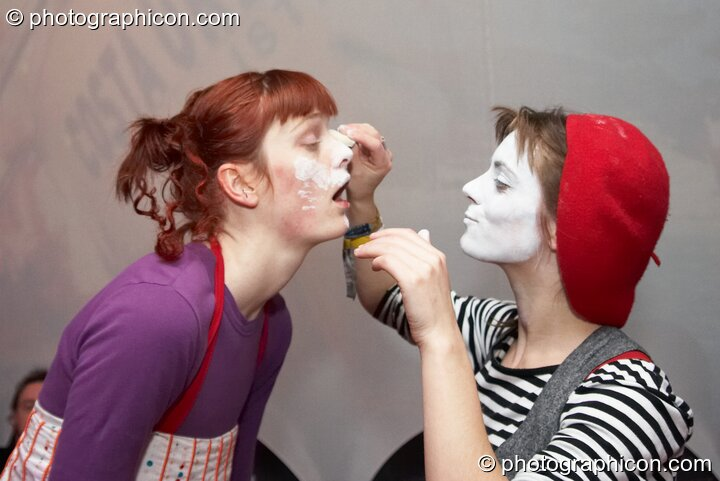 A woman white paints another woman's face at The Synergy Project. London, Great Britain. © 2007 Photographicon