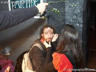 A man has his face painted under a sprig of mistletoe at The Synergy Project. London, Great Britain. © 2007 Photographicon