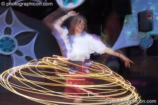 A woman spins an illuminated Hula Hoop leaving a skirt-shaped light trail  in the Liquid Records room at Luminopolis (formerly The Synergy Project). London, Great Britain. © 2008 Photographicon