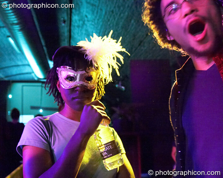 A woman in a mask drinks water while her male friend looks on in the entrance space at Luminopolis (formerly The Synergy Project). London, Great Britain. © 2008 Photographicon