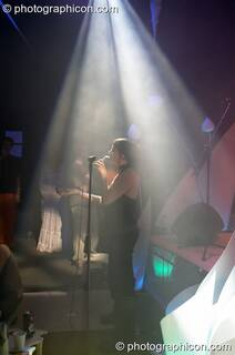 Woman vocalist illuminated by a downward cone of light in the Interdimensional Circus space at the Synergy Project. London, Great Britain. © 2005 Photographicon