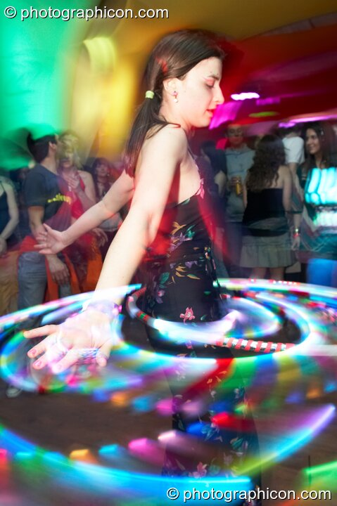 A woman skilfully twirls an illuminated Hoola Hoop in the Galactic Fantastic room at The Synergy Project. London, Great Britain. © 2008 Photographicon