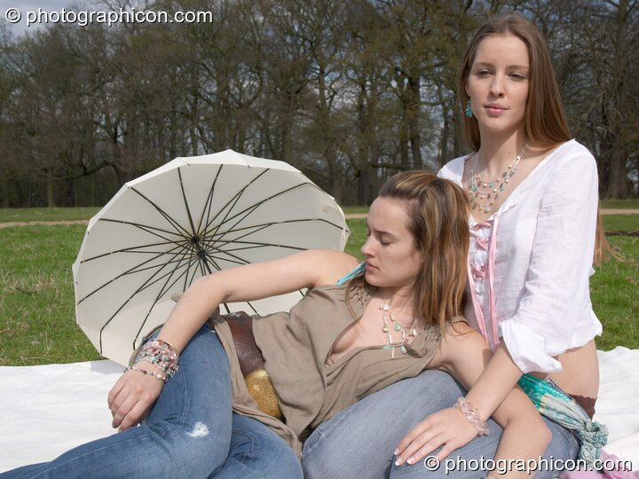 Two women sit together in the park with a parasol showing off their jewellery during a shoot for Aksinia Jewellery. Kingston Upon Thames, Great Britain. © 2005 Photographicon