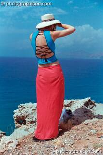 Ingrid wearing red andf blue outfit looks out to sea at Agios Pavlos. Greece. © 2002 Photographicon