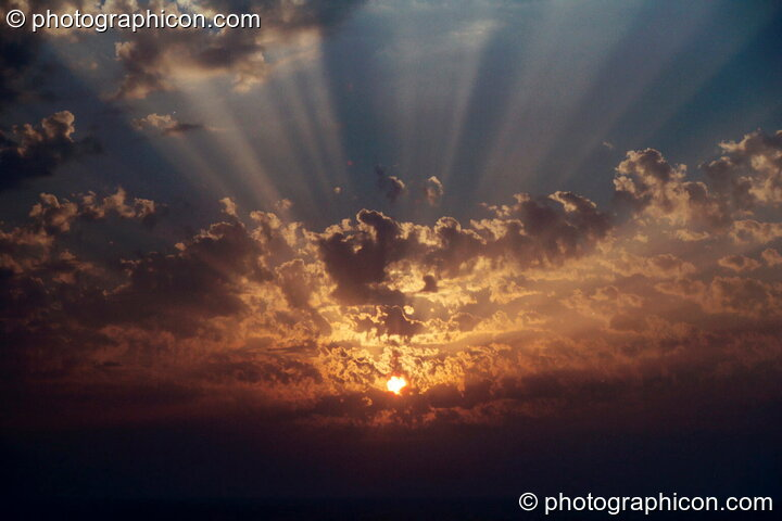 The setting sun through the gaps in the cloud at Agios Pavlos. Greece. © 2002 Photographicon