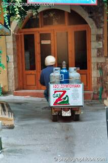 Man on scooter delivers large gas bottles in Rethymno. Greece. © 2002 Photographicon
