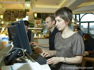 A man and woman use the free Internet terminals in the inSpiral Lounge organic cafe and multimedia venue. London, Great Britain. © 2008 Photographicon
