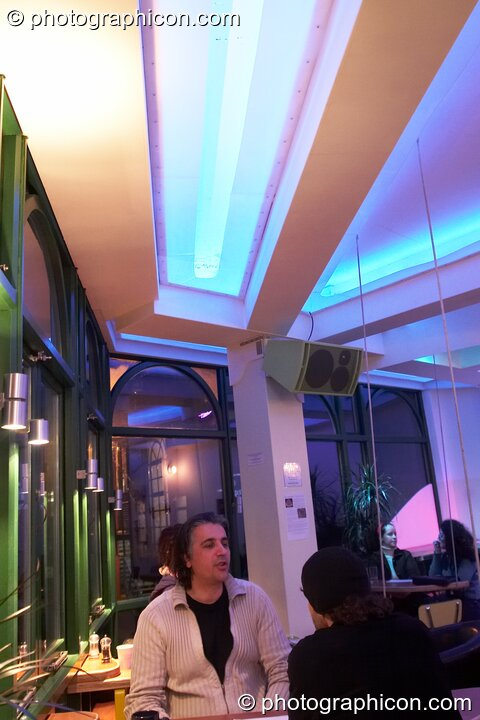A man sits at a table beneath the ceiling beams and LED lighting in the inSpiral Lounge organic cafe and multimedia venue. London, Great Britain. © 2008 Photographicon