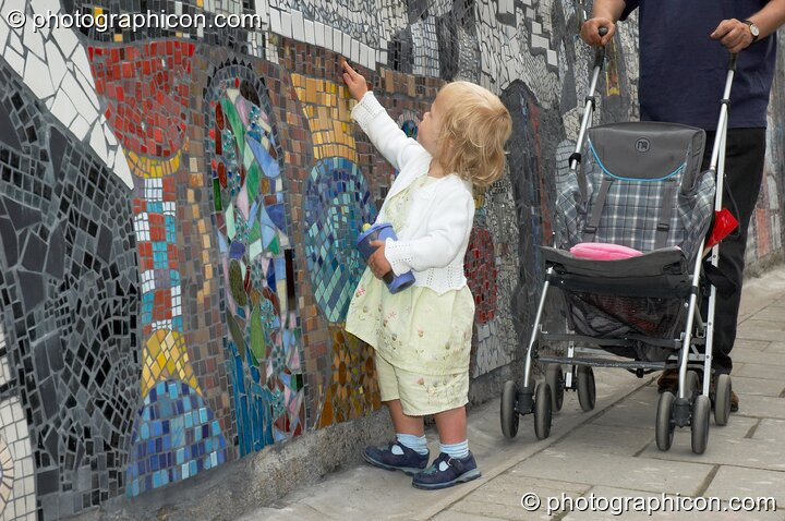 A small child examines the Save The World Club's Hundertwasser mosaic. Kingston Upon Thames, Great Britain. © 2005 Photographicon