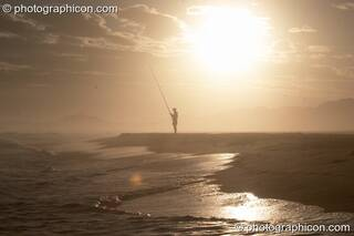 Profile of a distant fisherman with the sun reflected off sea that is lapping onto the beach at Boesmansriviermond - Eastern Cape, South Africa. © 2005 Photographicon