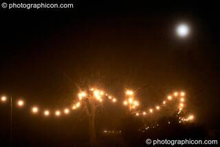 The moon in the mist above a long trail of fairy lights at the Lost Vagueness Summer Party 2004. Lewes, Great Britain. © 2004 Photographicon