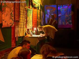 A man writes his thoughts on a stall in the Small World Stage at The Synergy Project. London, Great Britain. © 2007 Photographicon