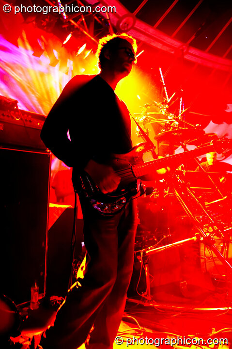 Chris Taylor (guitarist) of The Bays silhouetted against red and yellow lights while performing on the Main Stage at Glade Festival 2005. Aldermaston, Great Britain. © 2005 Photographicon