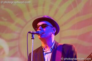 A member of the Alabama 3 stands in front of a projected sun motive with his Blues Brothers costume illuminated by blue light while performing on the Glade Stage at Glade Festival 2006. Aldermaston, Great Britain. © 2006 Photographicon
