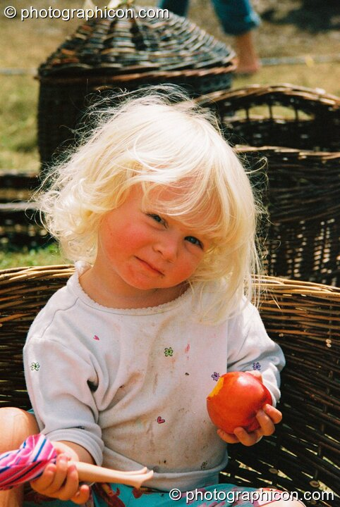 A little girl sits in a basket eating apple at Big Green Gathering 2003. Cheddar, Great Britain. © 2003 Photographicon