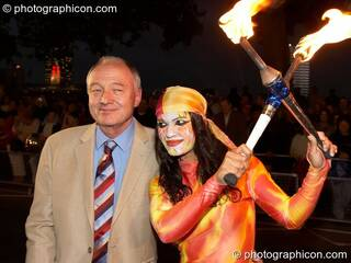 Ken Livingston (Mayor of London) is eyed by woman in leotard holding crossed fire sticks during the opening of the night carnival at the Thames Festival 2005. Great Britain. © 2005 Photographicon