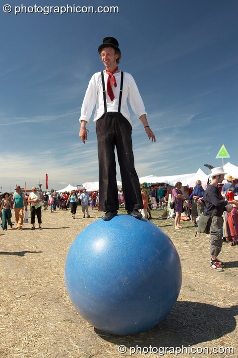 A man stands balanced on top of a large inflateable ball at Sunrise Celebration 2007. Yeovil, Great Britain. © 2007 Photographicon