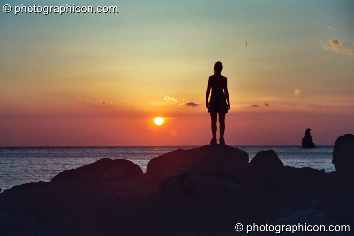 Woman looks out to sea, silhouetted by the golden sunset at Agios Pavlos. Greece. © 2002 Photographicon