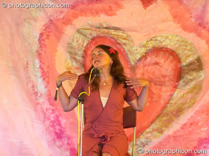 Jo Raphael performs the Vagina Monologues against a heart painted backdrop on the Eartheart Stage at Sunrise Celebration 2006. Yeovil, Great Britain. © 2006 Photographicon