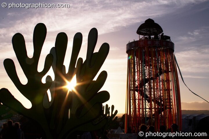 Silhouetted against the setting sun, a tall decorated scaffold tower with viewing platform rises above The Park next to cut-out sculptures of organic shapes at Glastonbury Festival 2008. Pilton, Great Britain. © 2008 Photographicon